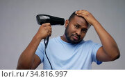 african american man with fan or hair dryer. Стоковое видео, видеограф Syda Productions / Фотобанк Лори
