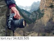 A female hand holds a camera against a caucasian mountain landscape. Стоковое фото, фотограф Zoonar.com/Ian Iankovskii / easy Fotostock / Фотобанк Лори