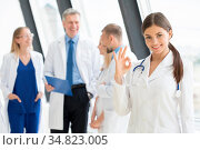 Female doctor showing Ok sign , team of doctors on background. Стоковое фото, фотограф Zoonar.com/Ivan Mikhaylov / easy Fotostock / Фотобанк Лори