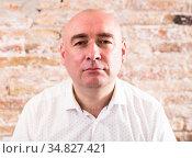portrait of bald adult mature man with emotions against brick wall. Стоковое фото, фотограф Татьяна Яцевич / Фотобанк Лори