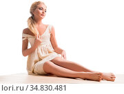 Beautiful blonde wearing beige corset sitting on the floor full-length... Стоковое фото, фотограф Zoonar.com/Andrey Guryanov / easy Fotostock / Фотобанк Лори