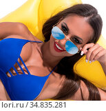 Sexy tanned brunette in nice blue bicini and color sunglasses smiling... Стоковое фото, фотограф Zoonar.com/Andrey Guryanov / easy Fotostock / Фотобанк Лори