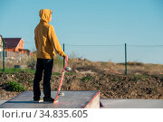 A teenager standing in a yellow hoodie holds a hand skateboard against... Стоковое фото, фотограф Zoonar.com/Ian Iankovskii / easy Fotostock / Фотобанк Лори