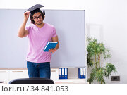 Young male student graduate wearing mortarboard. Стоковое фото, фотограф Elnur / Фотобанк Лори