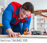 The young carpenter working with wooden planks. Стоковое фото, фотограф Elnur / Фотобанк Лори