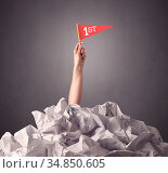 Female hand emerging from crumpled paper pile holding a red flag with... Стоковое фото, фотограф Zoonar.com/ranczandras / easy Fotostock / Фотобанк Лори