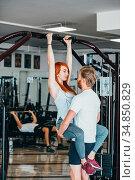Fitness coach help girlfriend on training in gym. Стоковое фото, фотограф Zoonar.com/Oleksii Hrecheniuk / easy Fotostock / Фотобанк Лори