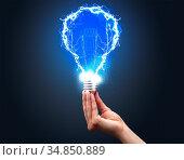 Hand holding shiny light bulb on dark background. New idea concept. Стоковое фото, фотограф Zoonar.com/rancz / easy Fotostock / Фотобанк Лори