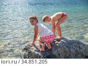 Young sister and brothet playing on a rock in front of a lake, smiling... Стоковое фото, фотограф Giovanni Gagliardi / easy Fotostock / Фотобанк Лори
