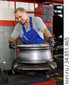 Mechanician restoring tire and disc of car wheel. Стоковое фото, фотограф Яков Филимонов / Фотобанк Лори