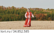 Feisty woman in red clothes standing on the field and posing with curved sword. Стоковое видео, видеограф Константин Шишкин / Фотобанк Лори