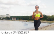 young woman in headphones running outdoors. Стоковое видео, видеограф Syda Productions / Фотобанк Лори
