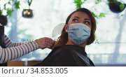 Female hairdresser putting cape on female customer wearing face mask at hair salon. Стоковое видео, агентство Wavebreak Media / Фотобанк Лори