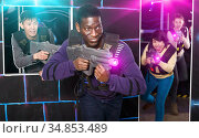 African man playing laser tag with friends. Стоковое фото, фотограф Яков Филимонов / Фотобанк Лори