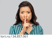 portrait of young asian woman making hush gesture. Стоковое фото, фотограф Syda Productions / Фотобанк Лори