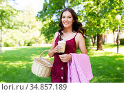 happy woman with picnic basket and coffee at park. Стоковое фото, фотограф Syda Productions / Фотобанк Лори