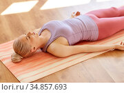 woman doing yoga corpse pose at studio. Стоковое фото, фотограф Syda Productions / Фотобанк Лори