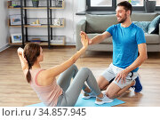 woman with personal trainer doing sit ups at home. Стоковое фото, фотограф Syda Productions / Фотобанк Лори