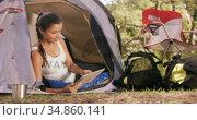 Woman sitting inside the tent and using a digital tablet. Стоковое видео, агентство Wavebreak Media / Фотобанк Лори