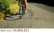 Female cyclist taking break after cycling on countryside road 4k. Стоковое видео, агентство Wavebreak Media / Фотобанк Лори