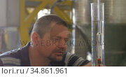 Male worker examining gin in measuring cylinder 4k. Стоковое видео, агентство Wavebreak Media / Фотобанк Лори