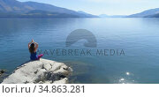 Woman performing yoga on at lake shore 4k. Стоковое видео, агентство Wavebreak Media / Фотобанк Лори