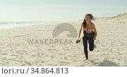 Female surfer with surfboard running on the beach 4K 4k. Стоковое видео, агентство Wavebreak Media / Фотобанк Лори