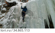 Ice climber climbing frozen cliff during winter 4k. Стоковое видео, агентство Wavebreak Media / Фотобанк Лори