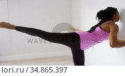 Woman stretching her leg at barre in fitness studio 4k. Стоковое видео, агентство Wavebreak Media / Фотобанк Лори