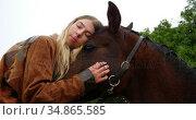 Woman kissing horse on wooden fence at ranch 4k. Стоковое видео, агентство Wavebreak Media / Фотобанк Лори