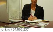 Businesswoman writing on a diary at desk 4k. Стоковое видео, агентство Wavebreak Media / Фотобанк Лори