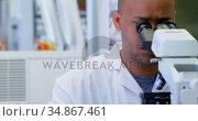 Scientist looking through microscope 4k. Стоковое видео, агентство Wavebreak Media / Фотобанк Лори