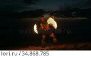 Fire juggler juggling fire sticks in the beach 4k. Стоковое видео, агентство Wavebreak Media / Фотобанк Лори