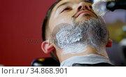 Barber applying shaving cream on client beard 4k. Стоковое видео, агентство Wavebreak Media / Фотобанк Лори
