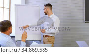 Executives discussing over whiteboard in conference room 4k. Стоковое видео, агентство Wavebreak Media / Фотобанк Лори