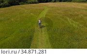 Woman riding bicycle in green field 4k. Стоковое видео, агентство Wavebreak Media / Фотобанк Лори