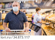 Senior man in protective mask with shopping trolley choosing pastries and products in supermarket. Стоковое фото, фотограф Татьяна Яцевич / Фотобанк Лори