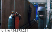 A worker works with a metal plate connected to the crane - gas cylinder and protective helmet in the foreground. Стоковое видео, видеограф Константин Шишкин / Фотобанк Лори