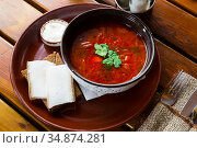 Ukrainian borscht red-beet soup on bowl, served with bread and salo. Стоковое фото, фотограф Яков Филимонов / Фотобанк Лори