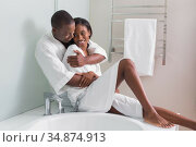 Couple sitting at edge of bath smiling at each other. Стоковое фото, агентство Wavebreak Media / Фотобанк Лори