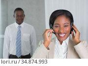 Call centre agent talking on the headset smiling at camera. Стоковое фото, агентство Wavebreak Media / Фотобанк Лори
