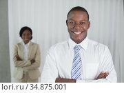 Smiling businessman looking at camera with colleague behind. Стоковое фото, агентство Wavebreak Media / Фотобанк Лори
