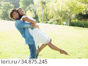 Hip young man lifting up his pretty girlfriend in the park. Стоковое фото, агентство Wavebreak Media / Фотобанк Лори