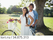 Hip young couple standing by fixed gear bike in the park. Стоковое фото, агентство Wavebreak Media / Фотобанк Лори