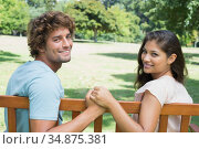 Cute young couple sitting on park bench together. Стоковое фото, агентство Wavebreak Media / Фотобанк Лори