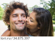 Pretty brunette kissing her boyfriend on the cheek in the park. Стоковое фото, агентство Wavebreak Media / Фотобанк Лори