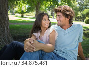 Young couple relaxing in the park smiling at each other. Стоковое фото, агентство Wavebreak Media / Фотобанк Лори