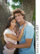 Young couple standing and embracing by large tree. Стоковое фото, агентство Wavebreak Media / Фотобанк Лори