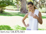 Fit woman standing with towel over shoulders in the park. Стоковое фото, агентство Wavebreak Media / Фотобанк Лори