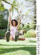 Pretty woman sitting on a swing in the park. Стоковое фото, агентство Wavebreak Media / Фотобанк Лори